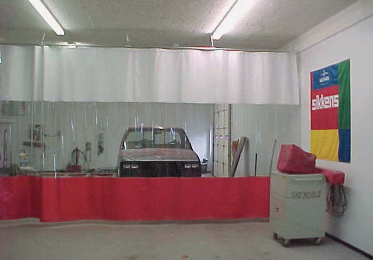 Paint booth divider curtains with a car seen through the clear section